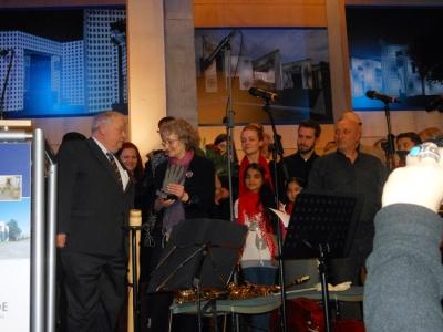 """Laudator Guntram Schneider und Annegret Keller-Steegmann. Im Hintergrund die Jugendlichen vom """"Bahtalo""""-Ensemble. Foto: Petra Grünendahl."""