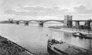 Die alte Eisenbahnbrücke von 1874 verband Hochfeld mit Rheinhausen. Der Kultushafen im Vordergrund war aus dem ehemaligen Trajekthafen der Rheinischen Eisenbahngesellschaft entstanden. Die neue Brücke von 1927 wurde direkt neben der alten Brücke gebaut (auf Rheinhauser Seite stehen noch die Brückentürme), im März 1945 gesprengt und bis 1949 in alter Form wieder aufgebaut. Foto: ZZB.