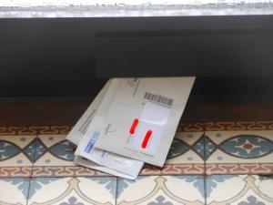 Korrekte Briefzustellung sieht anders aus: Einfach mal eben in den Zeitungsschlitz geschoben, wo man sie auch von außen gut rausziehenkann, anstatt odentlich in die Briefkästen (man müsste ja klingeln und es war sogar jemand da!) - so geht das heutzutage bei der Deutschen Post AG! Foto: Petra Grünendahl.