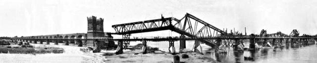 """Neben der zerstörten Fachwerk-Eisenbahnbrücke errichtete eine Pioniereinheit der US-Armee, das """"332nd Engineer General Service Regiment"""", die innerhalb von nur einer Woche eine Kriegsbrücke als Behelfsbrücke zur Rheinquerung (hier im Vordergrund des Bildes). Am 12. Mai 1945 ging die Konstruktion in Betrieb. Erst im Oktober 1949 konnte sie durch die wieder aufgebaute Eisenbahnbrücke ersetzt werden. Quelle: Wikipedia, gemeinfrei, bearbeitet von Carschten."""