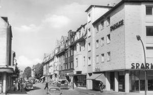 Blick von der Düsseldorfer Straße in die Fischerstraße in den 1960-er Jahren, bevor sie zur Basarstraße umgebaut wurde. Die Sparkasse rechts und die Marienapotheke links gibt es heute noch.