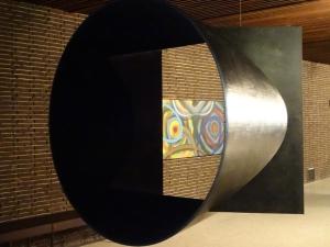 """Im Vordergrund die """"Quadratur des Kreises"""" von Troika, hinten an der Wand """"Moderne Zeiten"""" (2013) von Dejan Saric. Foto: Petra Grünendahl."""